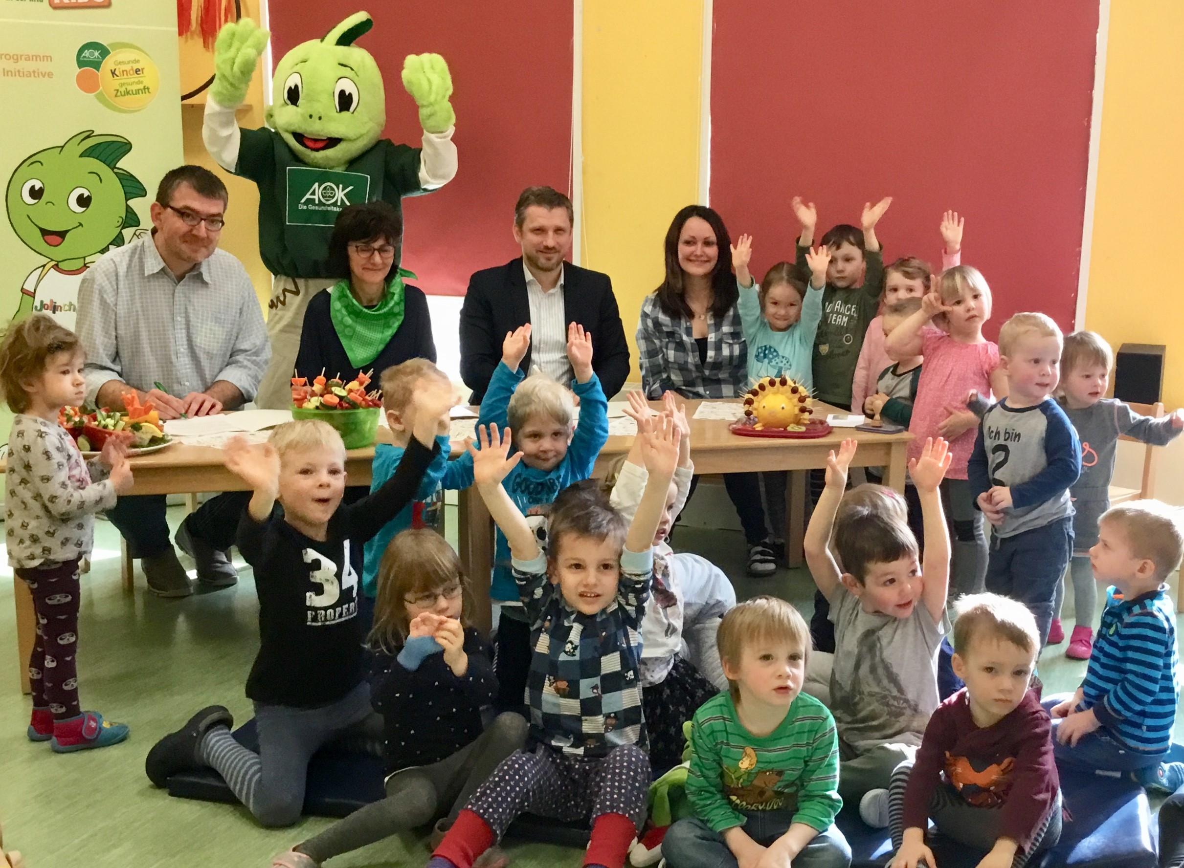 """v.l. Dirk Müller (Leiter der Kita), Susanne Neppert (AOK); Bürgermeister Sven Hause, Alexandra Krieg (Projektverantwortliche) unterzeichnen im Beisein der Kinder und von Projektmaskottchen """"Jolinchen"""" den Vertrag zum Gesundheitsprojekt."""