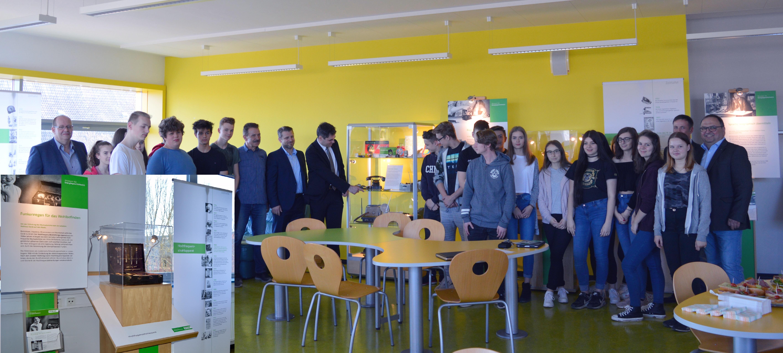 Dr. Tim S. Müller, Leiter des Museums für Energiegeschichte(n) (Bildmitte) erläutert den Schülern und Gästen Details der Smartphonevitrine