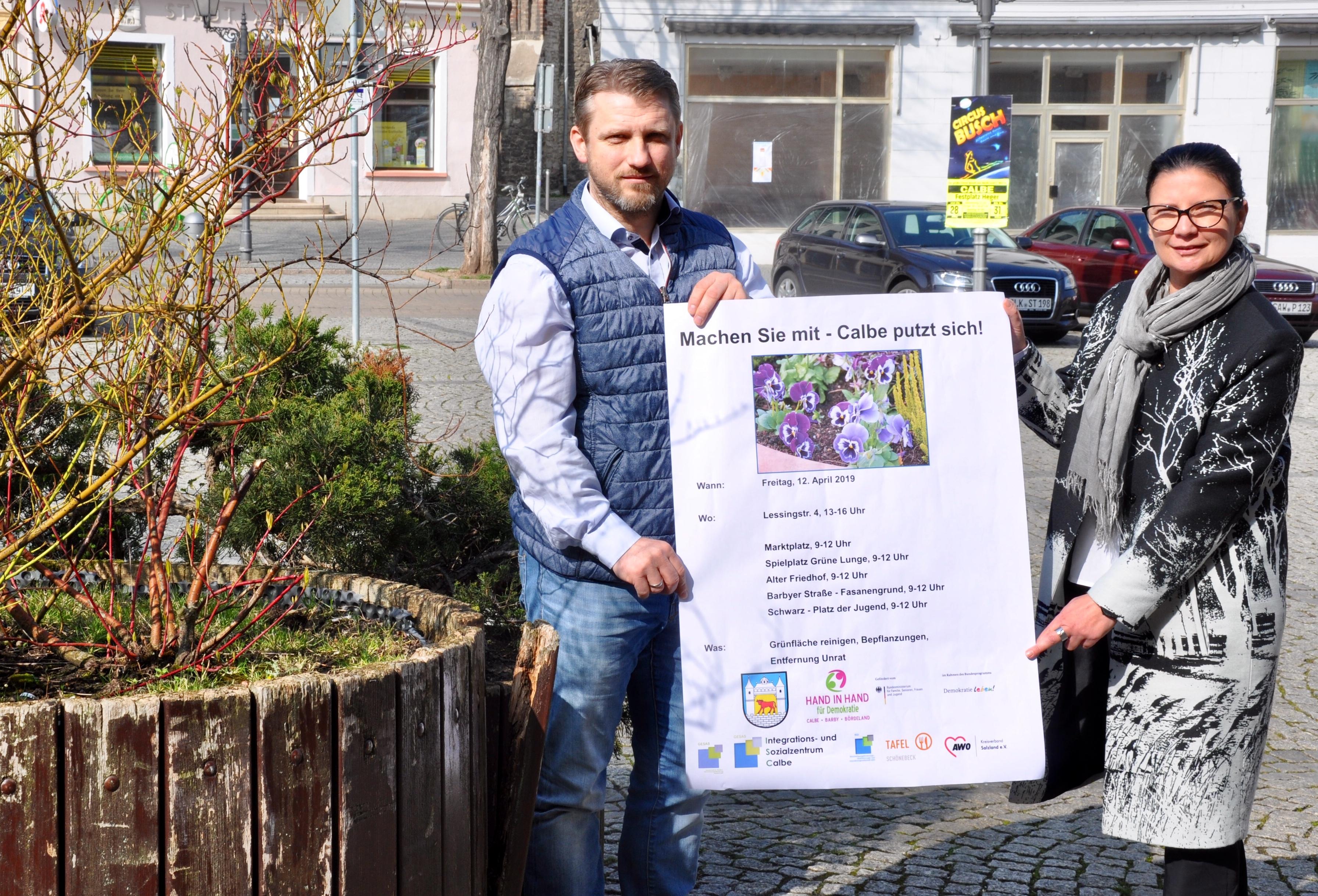 """Ines Grimm-Hübner Geschäftsführerin des AWO-Kreisverbandes Salzland e.V., und Bürgermeister Sven Hause präsentieren den Aufruf zur Aktion """"Calbe putzt sich!"""". Auch die sichtbar beschädigten Pflanzkübel auf dem Markt sollen erneuert werden."""