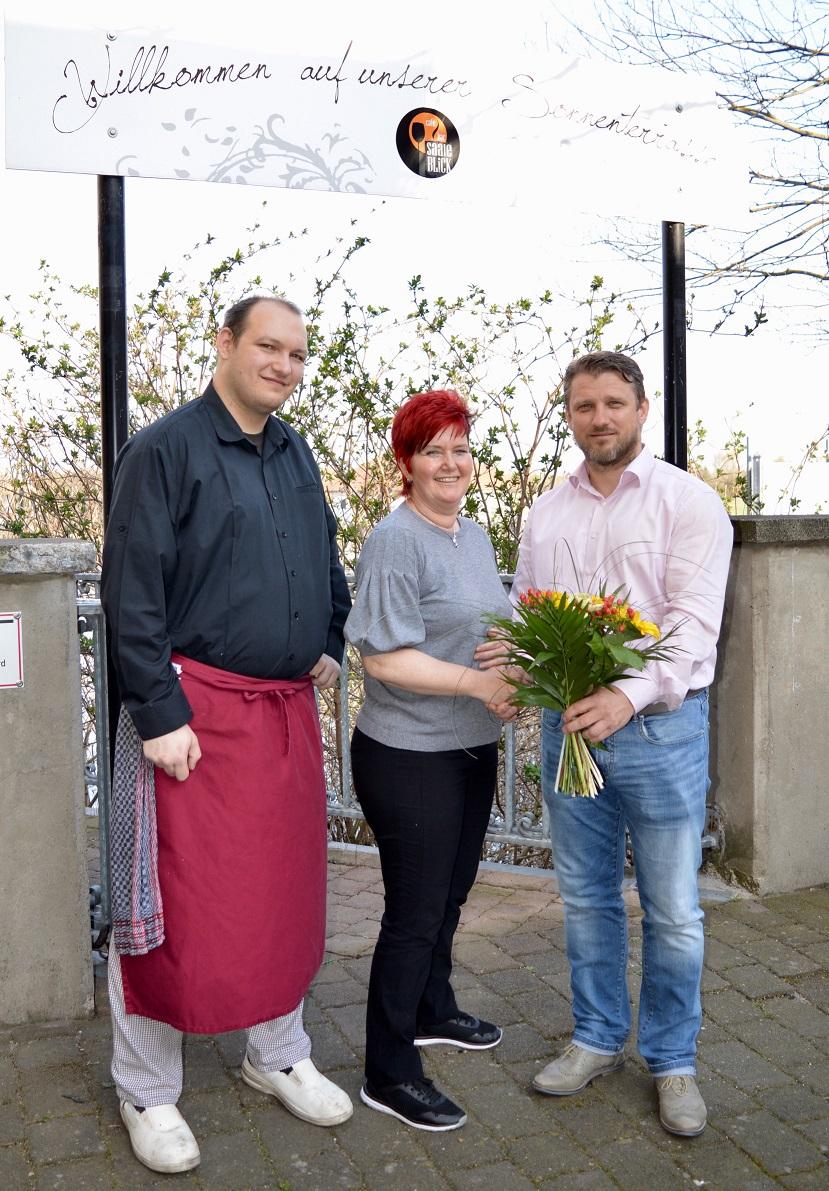 """Von recht: Bürgermeister Sven Hause beglückwünscht die Inhaberin Frau Andrea Beyer und Küchenchef Stefan Vogler mit einem Blumenstrauß zur Eröffnung des Restaurant und Café """"Saaleblick"""""""