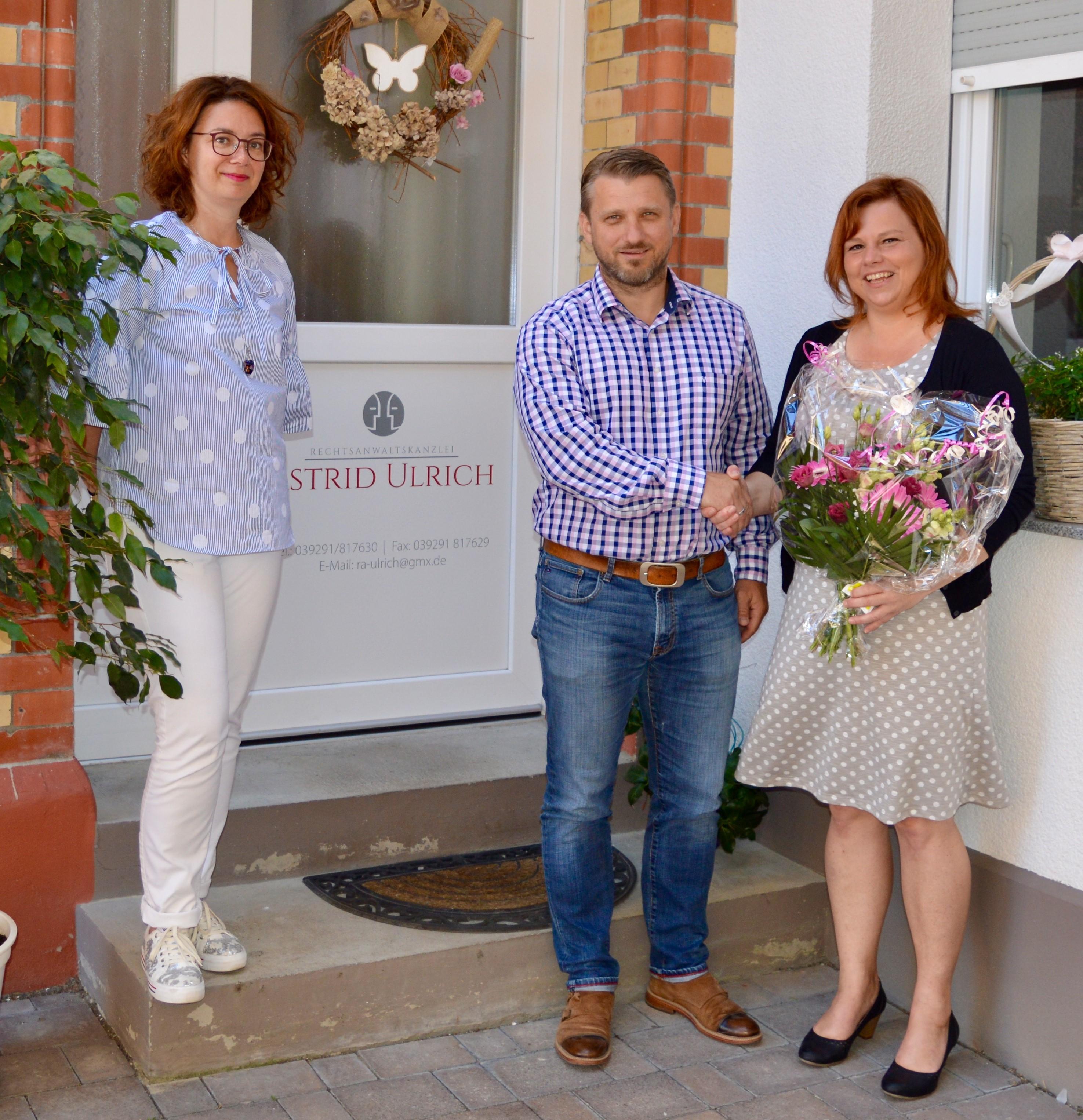 v.r. Bürgermeister Sven Hause beglückwünscht die Rechtsanwältin Frau Astrid Ulrich und Mitarbeiterin Frau Bratus mit einem Blumenstrauß zur Eröffnung der neuen Kanzlei.
