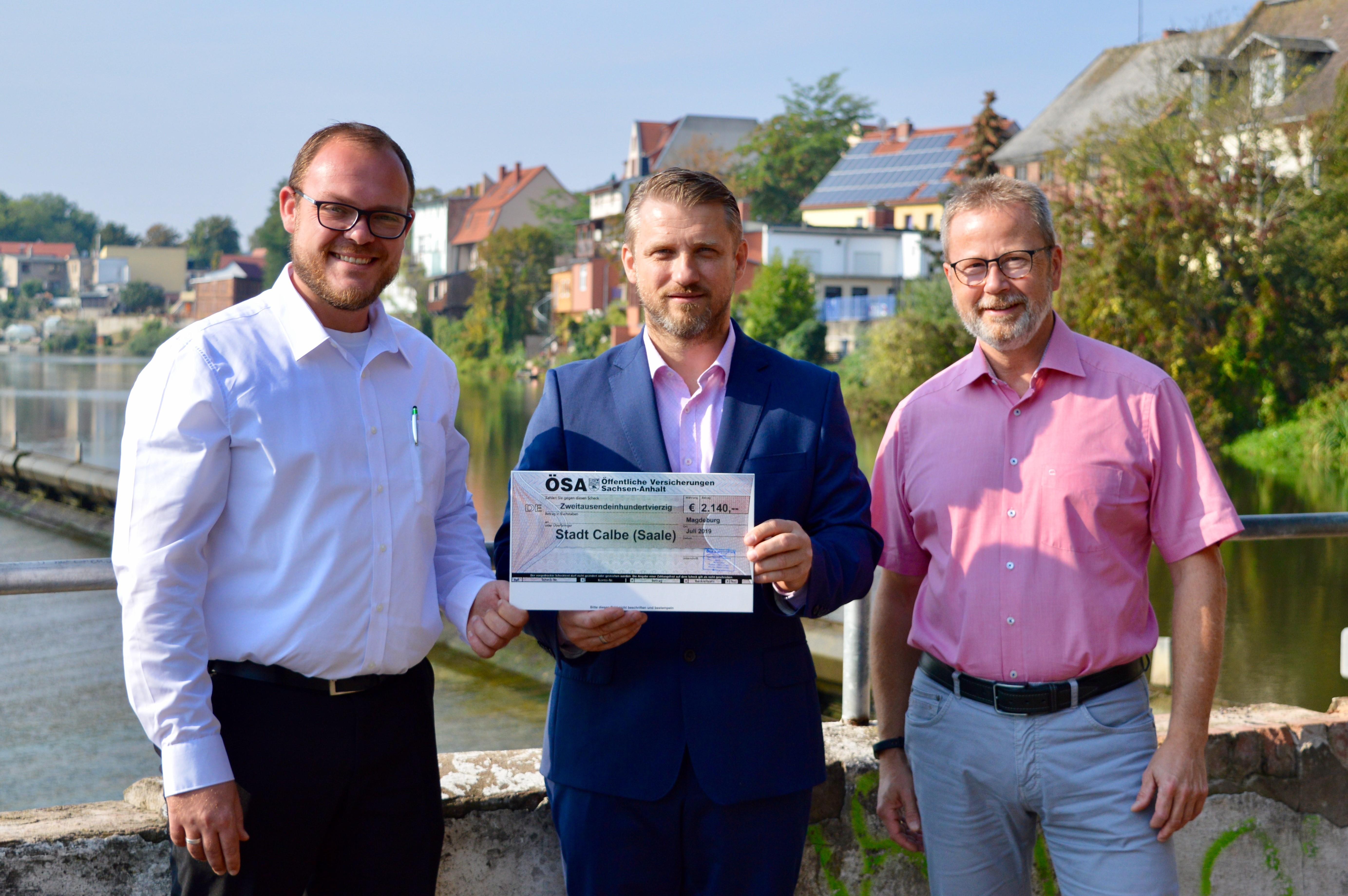v.l. ÖSA-Agenturleiter Stefan Riemann, Bürgermeister Sven und ÖSA Gebietsleiter Holger Günther bei der symbolischen Scheckübergabe.
