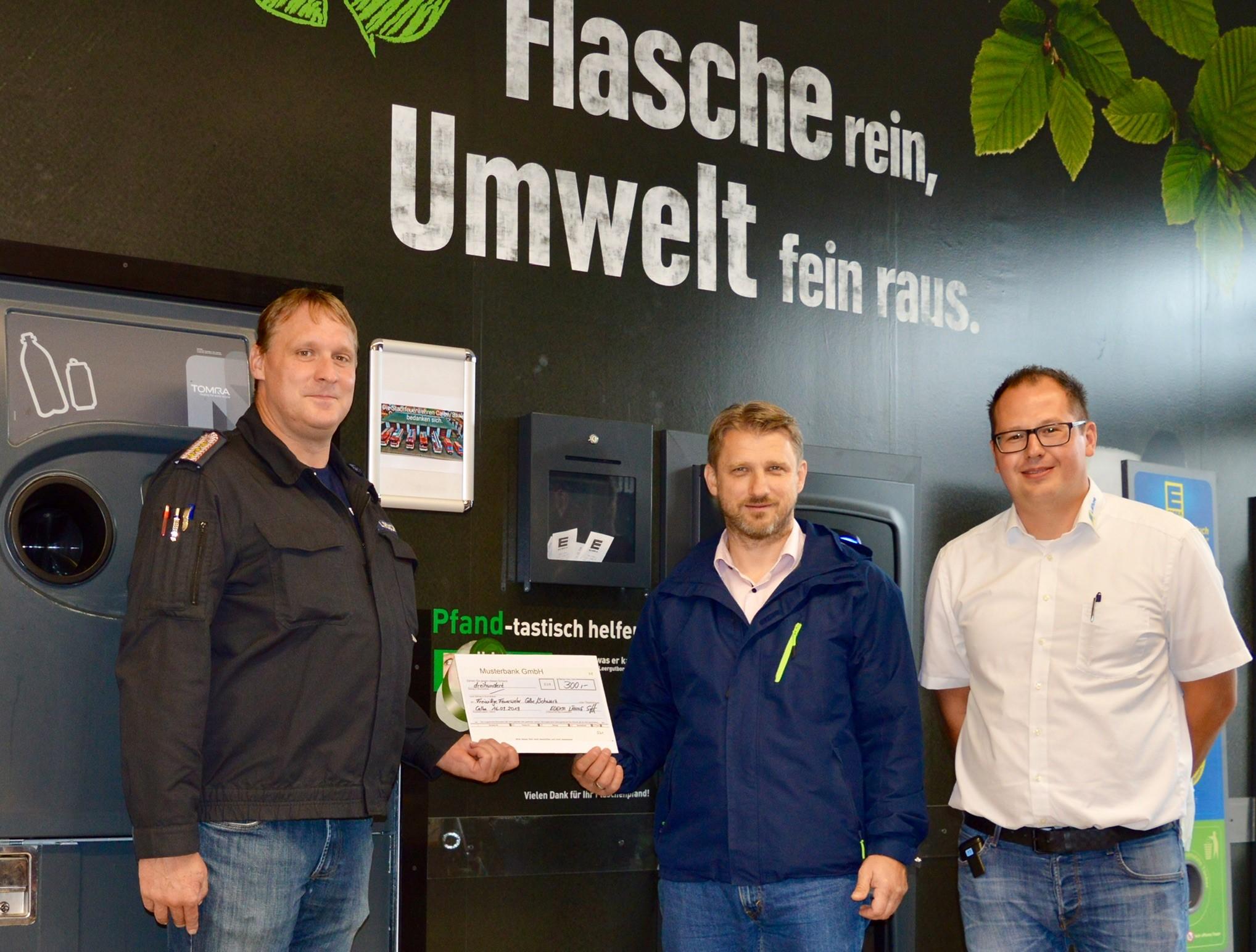 v.l. Stadtwehrleiter Calbe Lars Roschkowski und Bürgermeister Sven Hause erhalten den symbolischen Scheck  in Höhe von 300,00 Euro aus den Händen vom Marktinhaber Stephan Lähne.