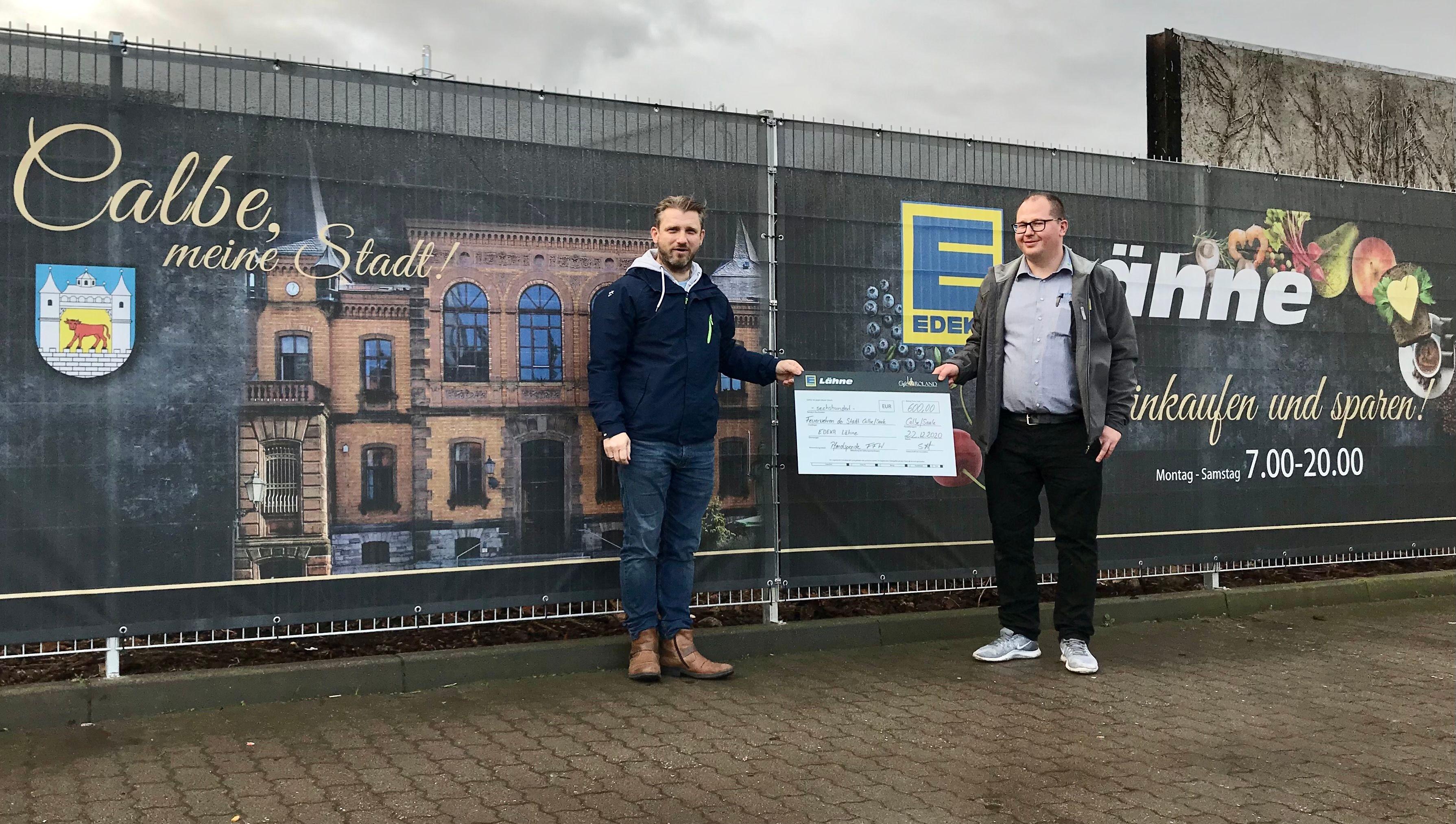 Bürgermeister Sven Hause (links) nimmt von EDEKA-Marktleiter Stephan Lähne die finanzielle Weihnachtsüberraschung für die Freiwilligen Feuerwehren Calbe und Schwarz entgegen.
