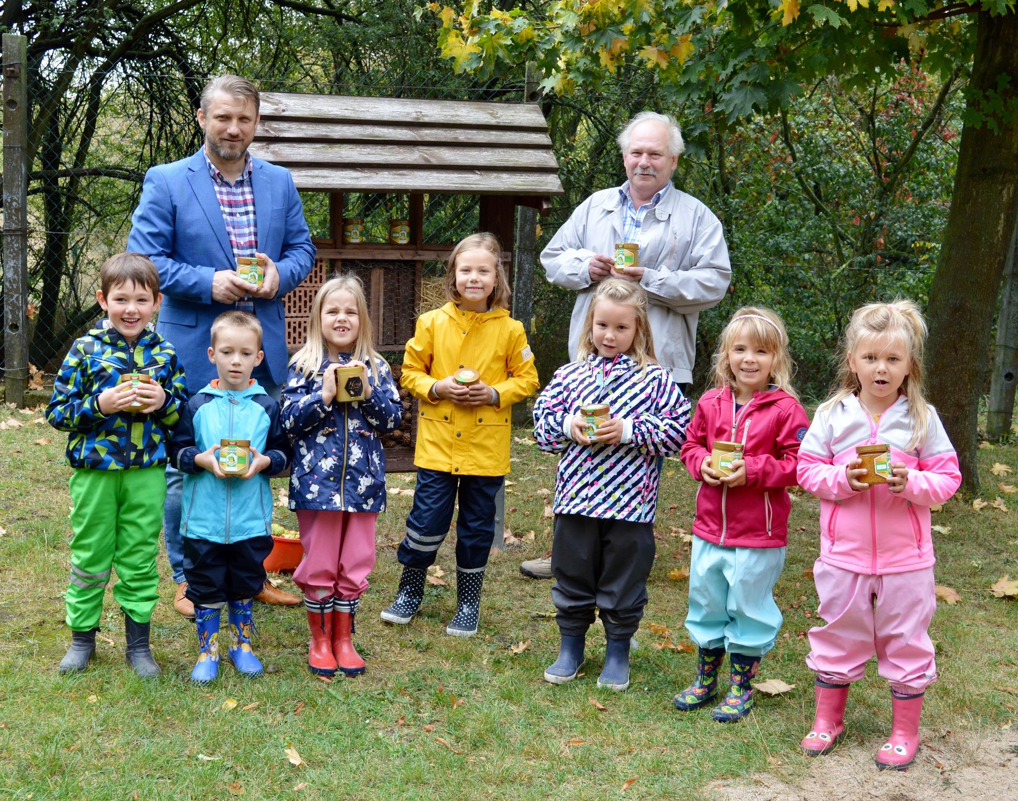 """Kinder der Kindertagesstätte """"Haus Sonnenschein"""" präsentieren stolz ihre Honigspenden zusammen mit dem Bürgermeister Sven Hause und Honigobmann Frank Kaina"""