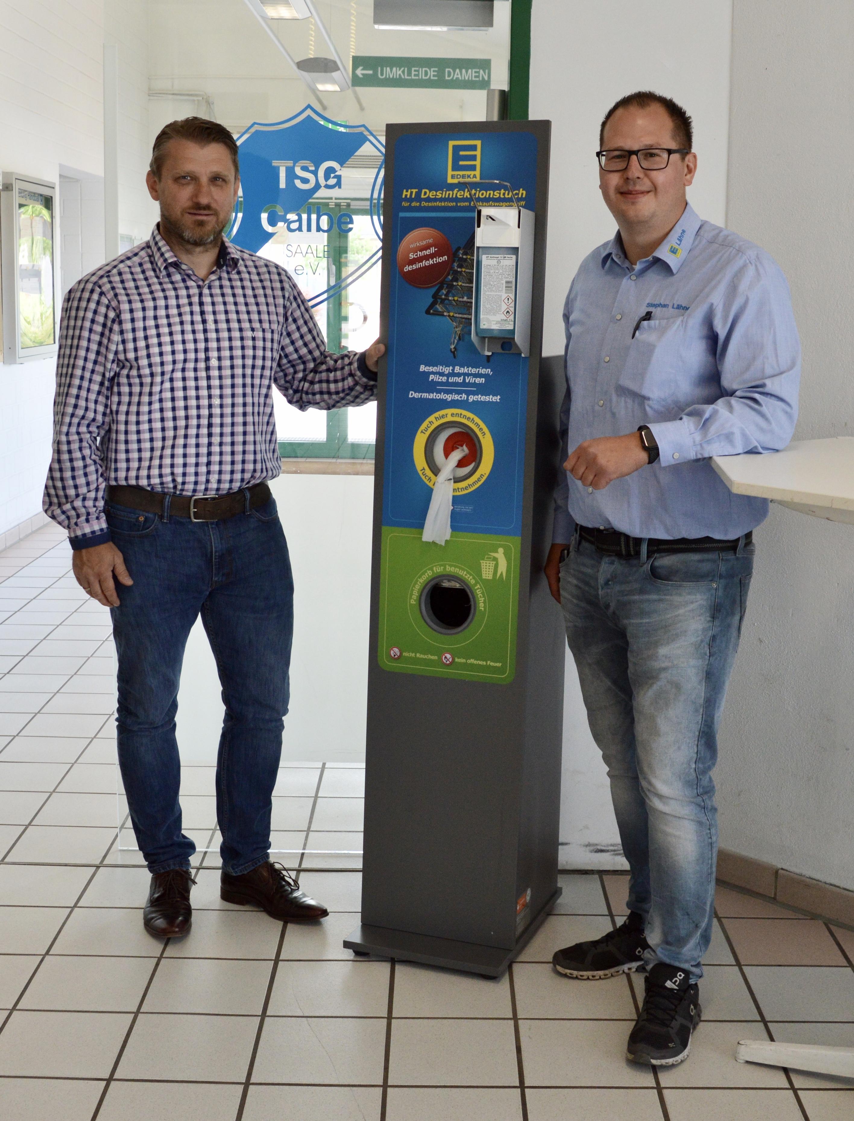 Stephan Lähne, Marktinhaber des EDEKA-Marktes in Calbe und Bürgermeister Sven Hause bei der Aufstellung und Inbetriebnahme der Hygienestation in der Hegersporthalle Calbe.