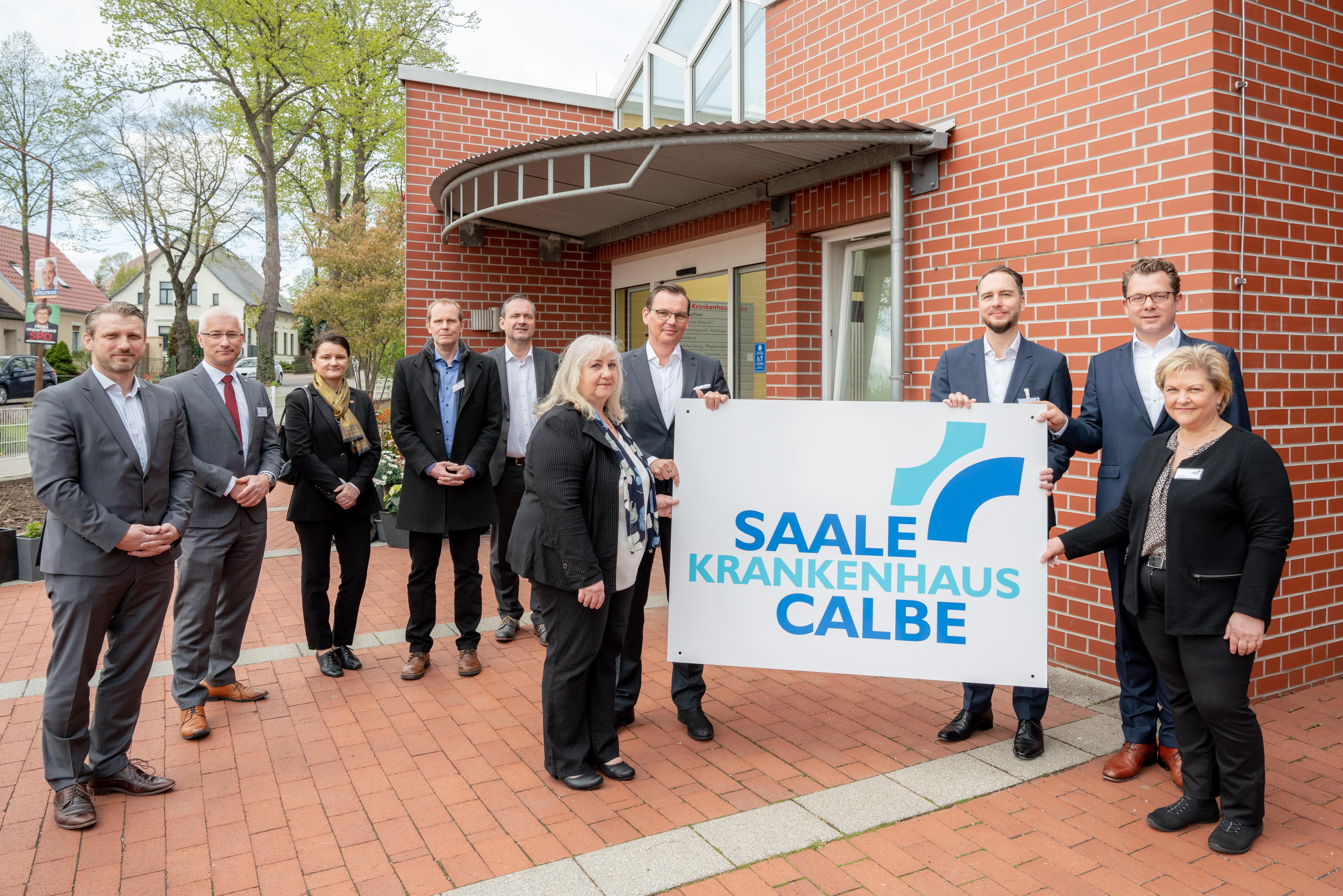"""Übergabe des neuen Eingangsschilds für das Krankenhaus Calbe, das seit dem 3. Mai 2021 einen neuen Namen hat: """"Saale-Krankenhaus Calbe – Klinik für Innere Medizin und Geriatrie/Altersmedizin""""."""